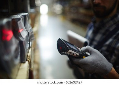 Side view closeup of bar code scanner in hand of unrecognizable warehouse worker doing inventory of stock