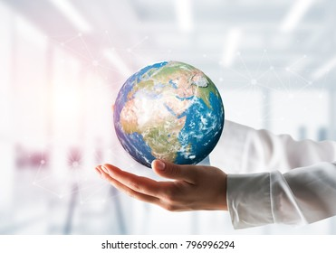 Side view closeup of businessman in shirt holding Earth globe in hands with sunlight and office view on background. Elements of this image are furnished by NASA.