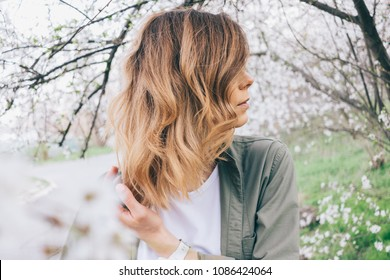 Side view close-up of female hairstyle long wavy bob. Young woman stands among blooming spring tree and touching her hair.