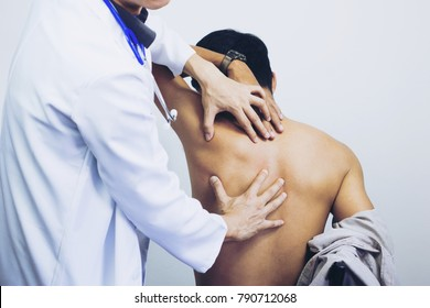 Side view close-up of a male physiotherapist examining mans back in the medical office. Doctor and patient man with a back pain.