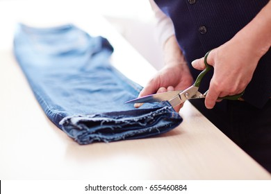 Side view closeup of man cutting jeans pants on tailors table in atelier