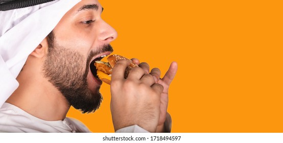 Side view of close-up portrait of young Arab man eating a burger. Hungry Arabic guy isolated on orange background eating a hamburger. Man wearing kandura and Ghutra eating junk food.