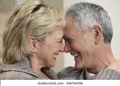 Side view closeup of romantic middle aged couple with heads together