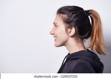 Side view closeup of smiling woman standing by white wall looking forward