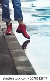 side view closeup of young Caucasian woman feet with red short rubber boots and blue jeans standing on sidewalk and stepping into a puddle of water after rain on a city street