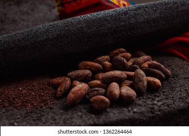 Side view of cocoa and cacao powder on a traditional metate, used in mexican indigenous culture to extract the powder from the cacao beans or cacao nibs