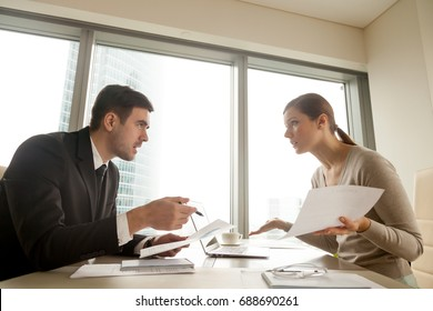 Side view of colleagues arguing at workplace, executives disagree about papers, found error in contract, mistake in paperwork, business partners having claims to documents, disputing over agreement