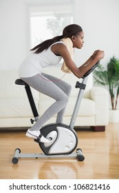 Side view of a concentrated black woman doing exercise bike in a living room