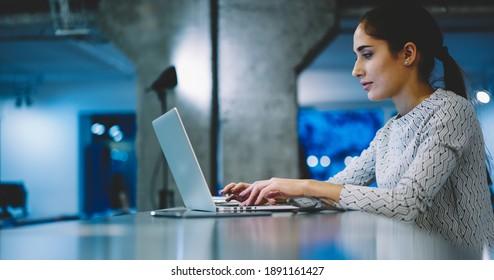 Seitenansicht des weiblichen Konzentrats in Gelegenheitsartikeln, die auf dem Netbook tippen, während der Arbeit an einem neuen Projekt am Schreibtisch im modernen Arbeitsbereich