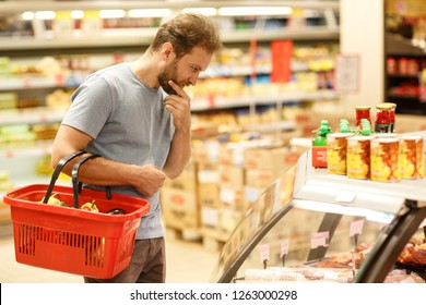 Side view of concentrated man thinking and looking down at glass case with products. Bearded customer holding red basket on hand and another hand putting on chin. Buyer do shopping in grocery store.