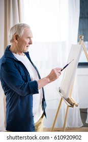 Side view of concentrated senior man painting picture on easel at home