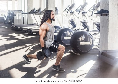 Side view of concentration young adult sportman athlete with long curly hair working out in gym, squating on one knee and holding two dumbbells, doing exercises for legs, squatting. indoor