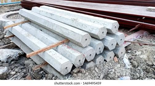 Side view of concrete pole piles preparing for construction.
