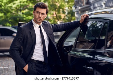 Side view of confident business man in formalwear and eyewear leaning at the car and looking at away.