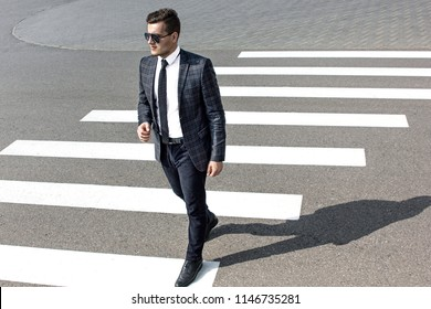 Side view of confident businessman passing crosswalk in modern district of megalopolis choosing direction, serious male entrepreneur cros...
