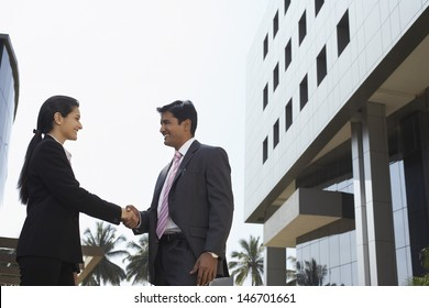 Side view of confident businesswoman and businessman shaking hands outdoors