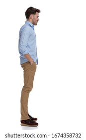 Side view of confident casual man holding both hands in pockets while wearing shirt and standing on white studio background