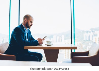 Side view of confident male proud ceo in formal wear browsing internet websites with financial news on smartphone device connected to free wifi.Businessman sending notification sitting near copy space