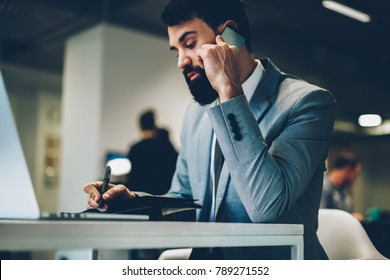 Side view of confident proud ceo with beard dressed in stylish formal apparel writing down financial accountings while talking with business partner on smartphone device working in office indoors