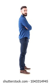 Side view of confident serious cool man with crossed arms looking at camera. Full body isolated on white background.