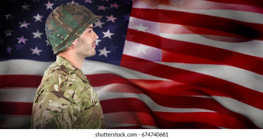 Side view of confident soldier in uniform standing against american flag