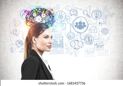 Side view of confident and successful young businesswoman with long fair hair standing near concrete wall with colorful brain sketch and business icons drawn on it. Concept of planning