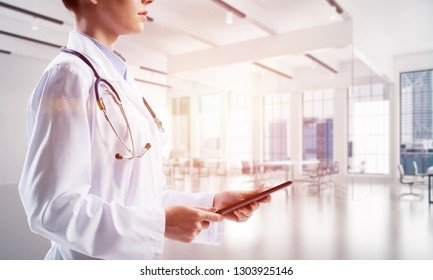 Side view of confident woman doctor in white sterile suit holding tablet in hands while standing indoors of white hospital room with sunlight on background. Medical industry concept
