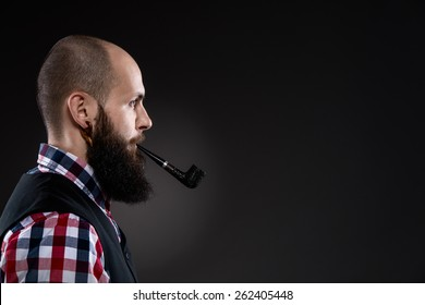 Side view of confident young bearded man in checkered shirt is smoking a pipe