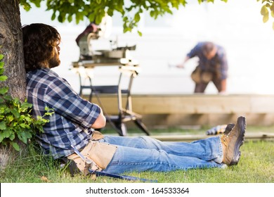 Side view of construction worker leaning on tree trunk while coworker working in background