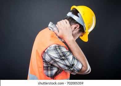 Side view of constructor holding back neck like hurting.