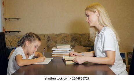 Side view of content woman and little girl doing school homework together at table in living room