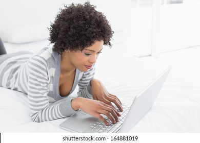 Side view of a content young woman using laptop in bed at home