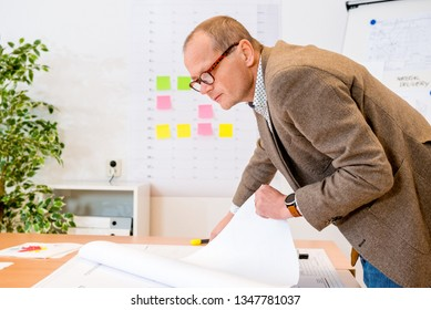 Side view of contractor analyzing the plan on blueprint at workplace