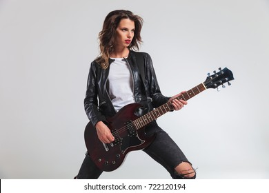 side view of a cool woman guitarist playing electric guitar on grey background