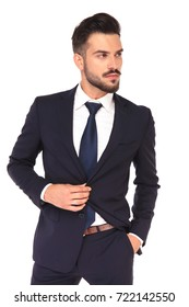 side view of a cool young business man buttoning his suit and looks away on white background