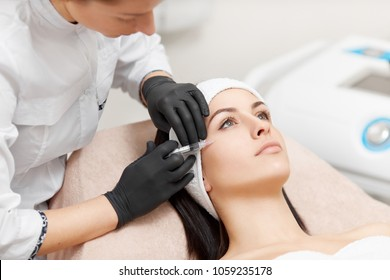 Side view of cosmetology specialist holding syringe in hands and doing injection. Attractive client lying and getting anti-wrinkle and rejuvenating procedures. Interior of modern beauty salon.