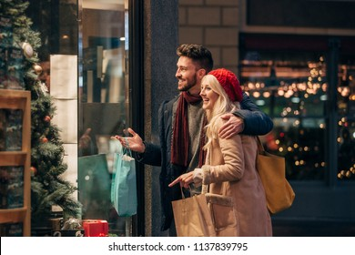Side view of a couple doing some window shopping at christmas. The mid adult male has his arm around the mid adult female and they are talking about wats in the window.