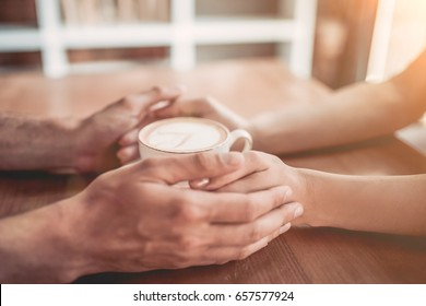 Side view of couple in love holding hands with coffee on wooden table.