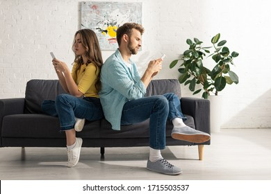 Side view of couple using smartphones while sitting back to back on sofa