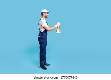 Side view, courier in blue uniform giving groceries bag and smiling friendly, carrying parcel with goods ordered online. Professional delivery service, food purchase. indoor studio shot isolated