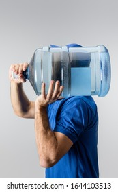 Side view of courier carrying on shoulder bottled water isolated on grey