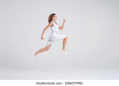 Side view of crazy joyful girl in summer dress jumping isolated over background