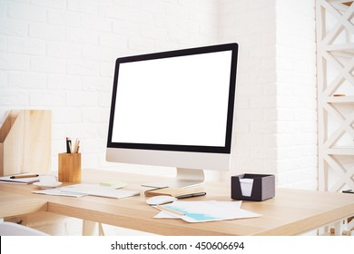 Side view of creative designer workplace with blank white computer monitor, various stationery and decorative items on brick wall background. Mock up