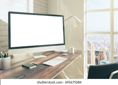 Side view of creative designer workplace with empty white pc computer monitor placed on desktop with coffee cup, supplies and other items. Brick wall background. Mock up, 3D Rendering