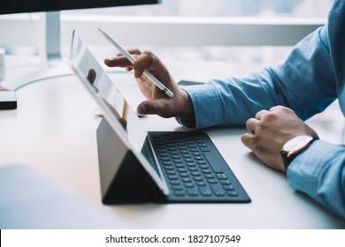 Seitenansicht anonymer männlicher Hände mit Armbanduhr mit modernem drahtlosem Tablet mit Tastatur und Stylus während der Arbeit im modernen Büro