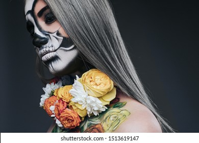 Side view of crop attractive woman with black and white ghost makeup and colorful flowers around neck on dark gray background