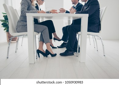 Side view, cropped, bottom view portrait of stylish, attractive, classy business people's legs under table, in suits, sitting in work place, station, having conference, consulting, clients, brokers