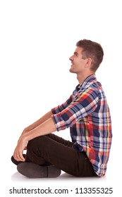 side view of a cross legged casual young man looking up, away from the camera and holding his hands on his knees