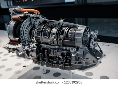 Side view cross section of automatic transmission gearbox on blurry background.