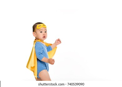side view of cute asian toddler boy in superhero costume isolated on white
